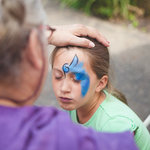 A butterfly wing begins to unfurl in face paint.